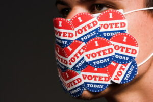 Man with face mask with many I voted today stickers. Coronavirus and American presidential elections concept.
