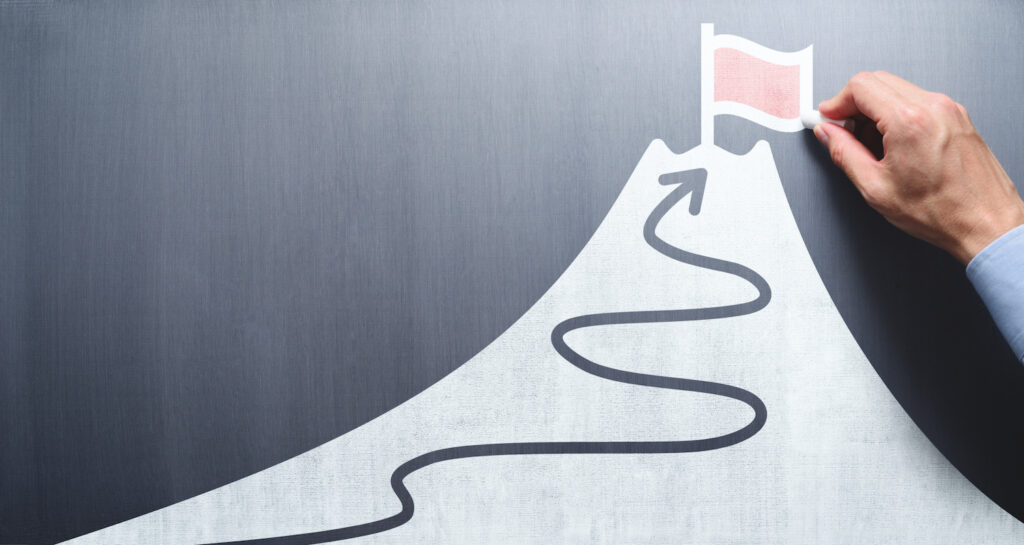 selling covered calls: man drawing a hill with a flag on top