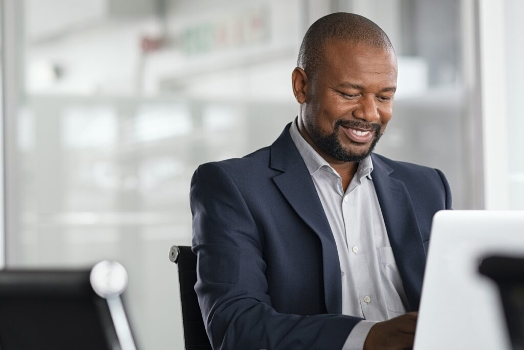 Portfolio diversification: Businessman smiles while typing on his computer