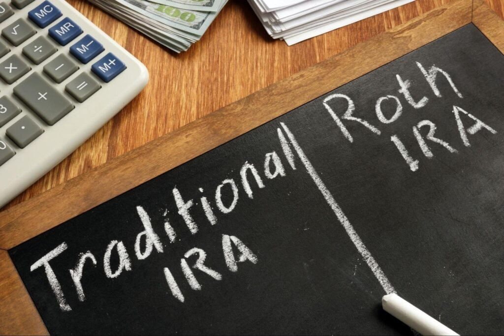Traditional IRA and Roth IRA written on a blackboard on top of a wooden table