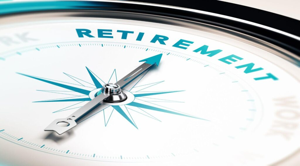best investments for retirement: Close up shot of a compass pointing to the word retirement