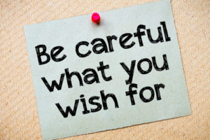 Be careful what you wish for Message. Recycled paper note pinned on cork board. Concept Image
