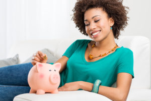 Young Girl Lying On Couch And Putting Coin In Piggybank