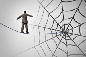 Businessman trap business concept with a tightrope walker walking on a wire leading to a giant spider web as a metaphor for adversity and deception of being lured to a financial ambush or recruiting new career candidates.
