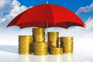 Financial stability, business success and insurance concept: stacked golden coins covered by red umbrella against blue sky with clouds on white background with reflection effect