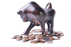 A strong, triumphant bull atop a pile of coins, signifying an optimistic or bullish foreign currency (forex) market.