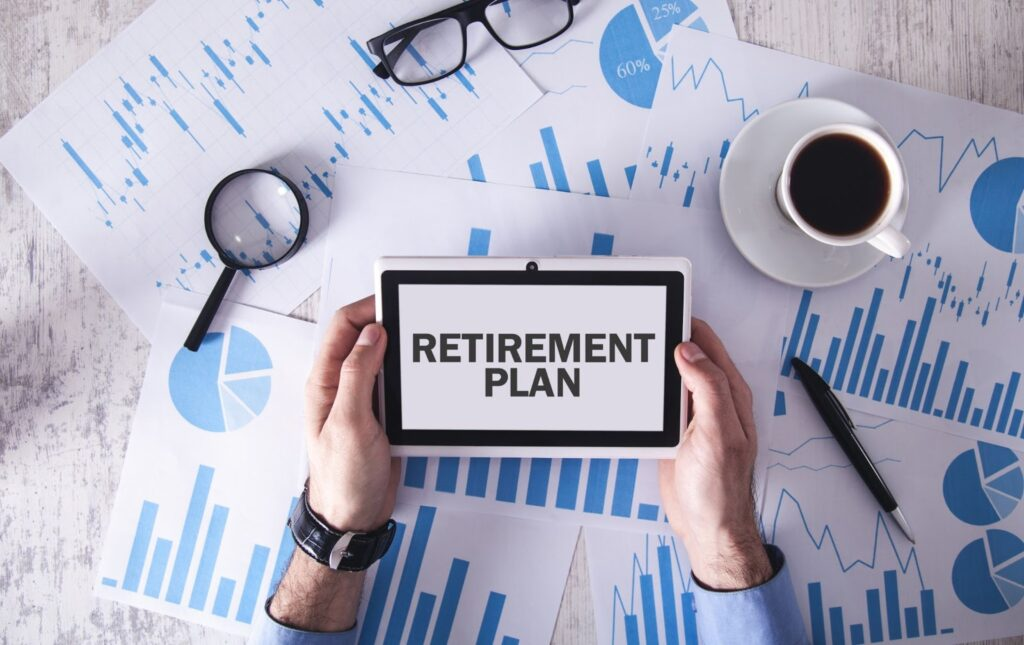 """Dividend growth investing: A closeup of two hands holding a sign that says, """"Retirement plan"""""""