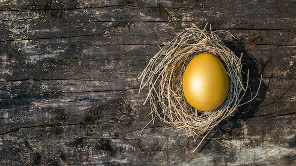Golden egg in a nest on a wooden surface