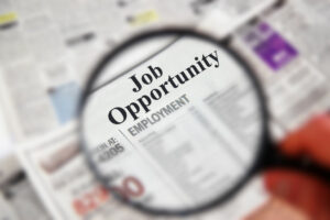 Magnifying glass over a newspaper classified section with  Job Opportunity  text