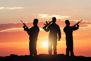 Silhouette Of Soldiers With Rifles Against Dramatic Sky