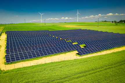 View of solar panels and wind turbines in field