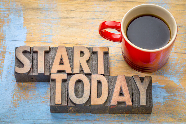 START TODAY in wooden blocks beside a mug of coffee