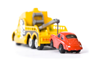 Red car being towed away by yellow tow truck (1)