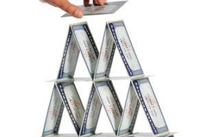 Man'a hand building house of cards with social security cards isolated over white background