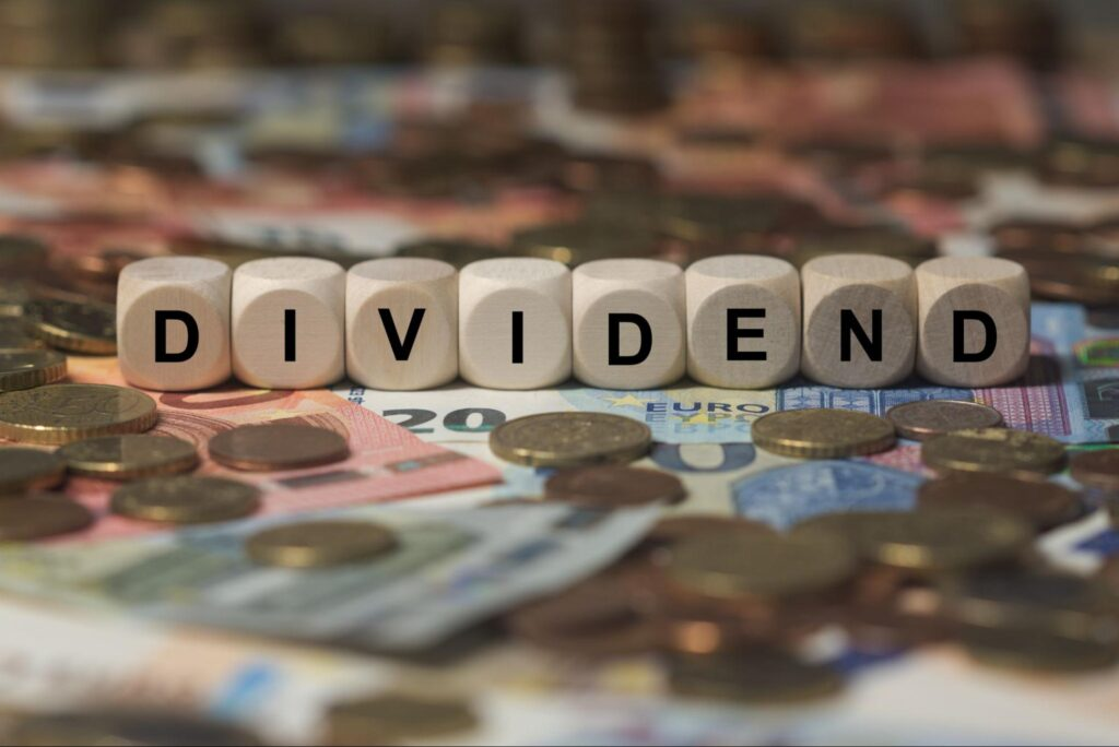 capital gains yield: dividend spelled in cubes with letters surrounded with lots of money
