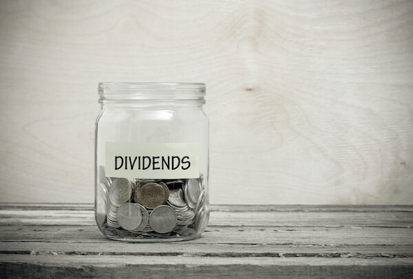 dividend rate: coins in a mason jar labeled with DIVIDENDS