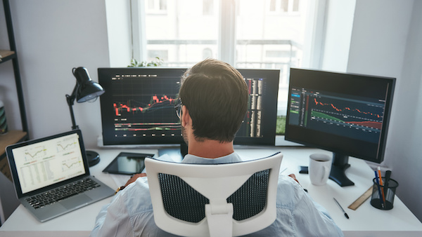 Traders guide: guy looking at multiple monitor