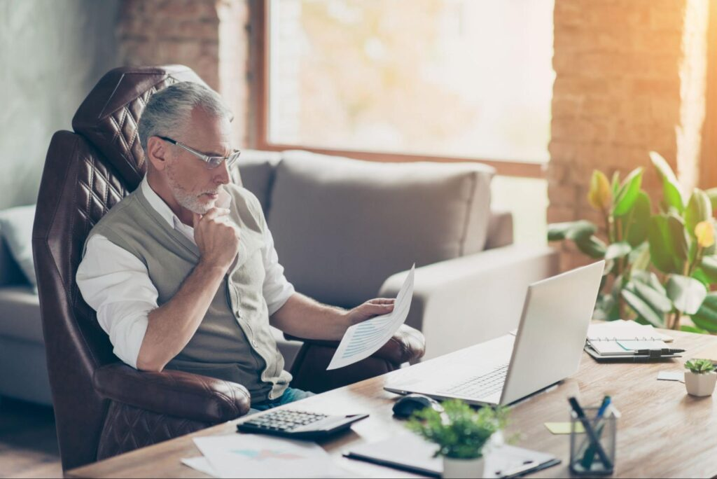 old man looking at his laptop while holding a paper
