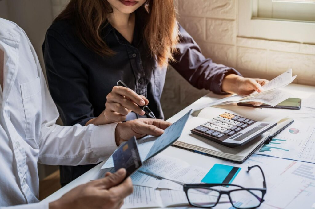 income investing: Man and woman calculating expenses