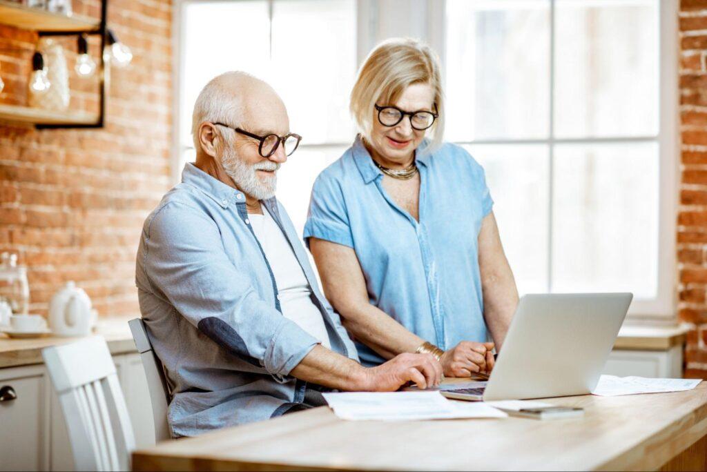 best long term dividend stocks: elderly couple looking at paperwork