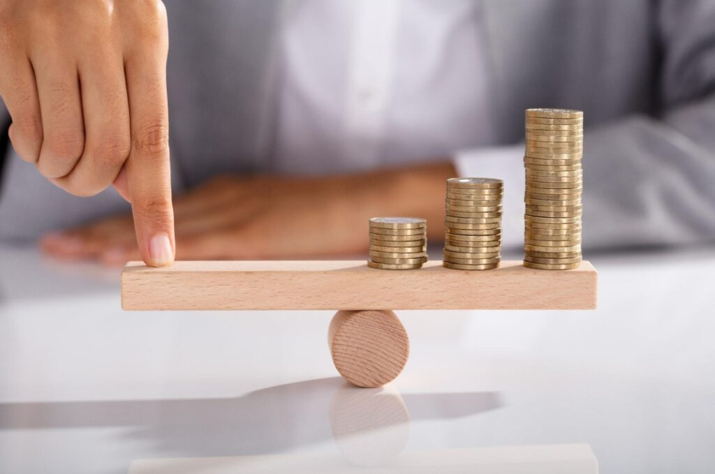 what is dividend income: Person balancing coins on top of a wooden seesaw
