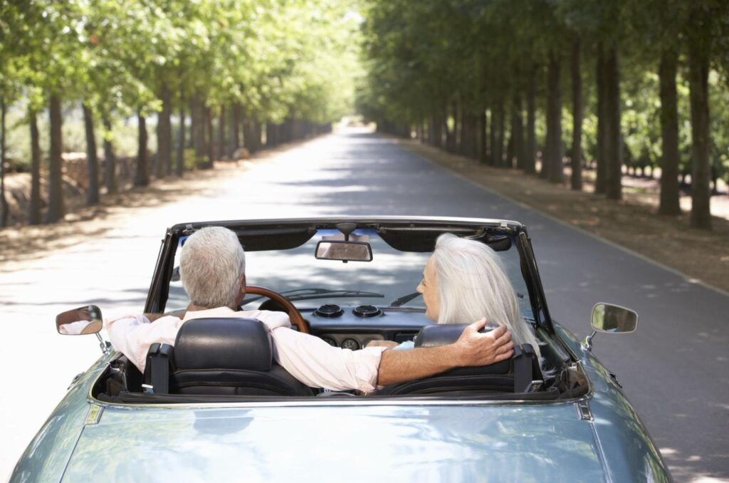 Elderly couple driving around in a convertible