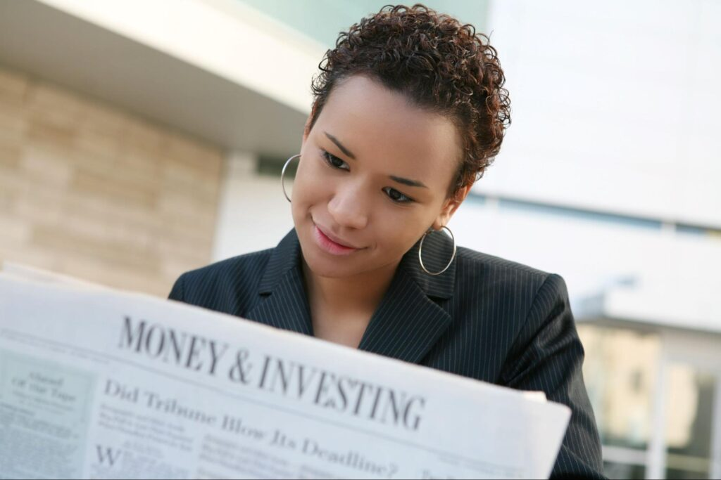 high yield investments: woman reading a newspaper
