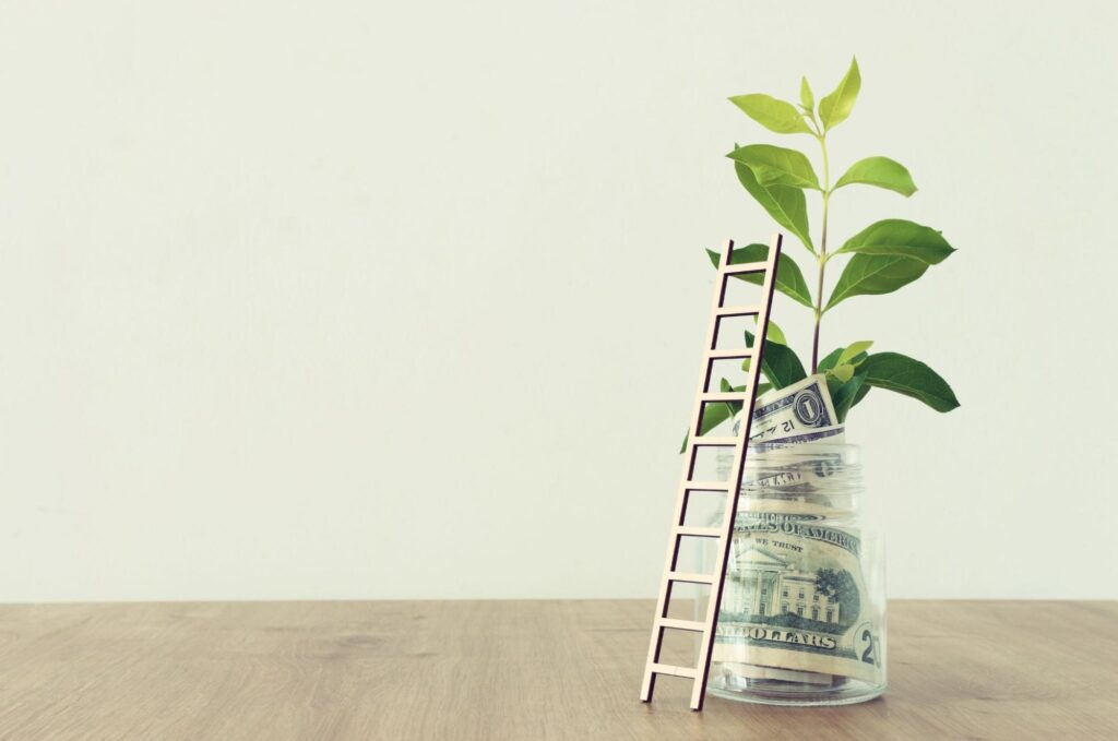 income investing: Money and a plant inside a jar with a ladder leaning against it on top of a wooden surface
