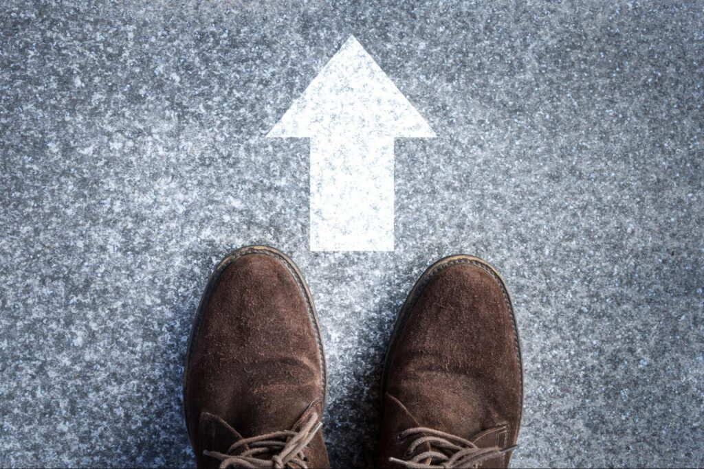 monthly dividend stocks: Shoes on a concrete floor with an arrow pointing up