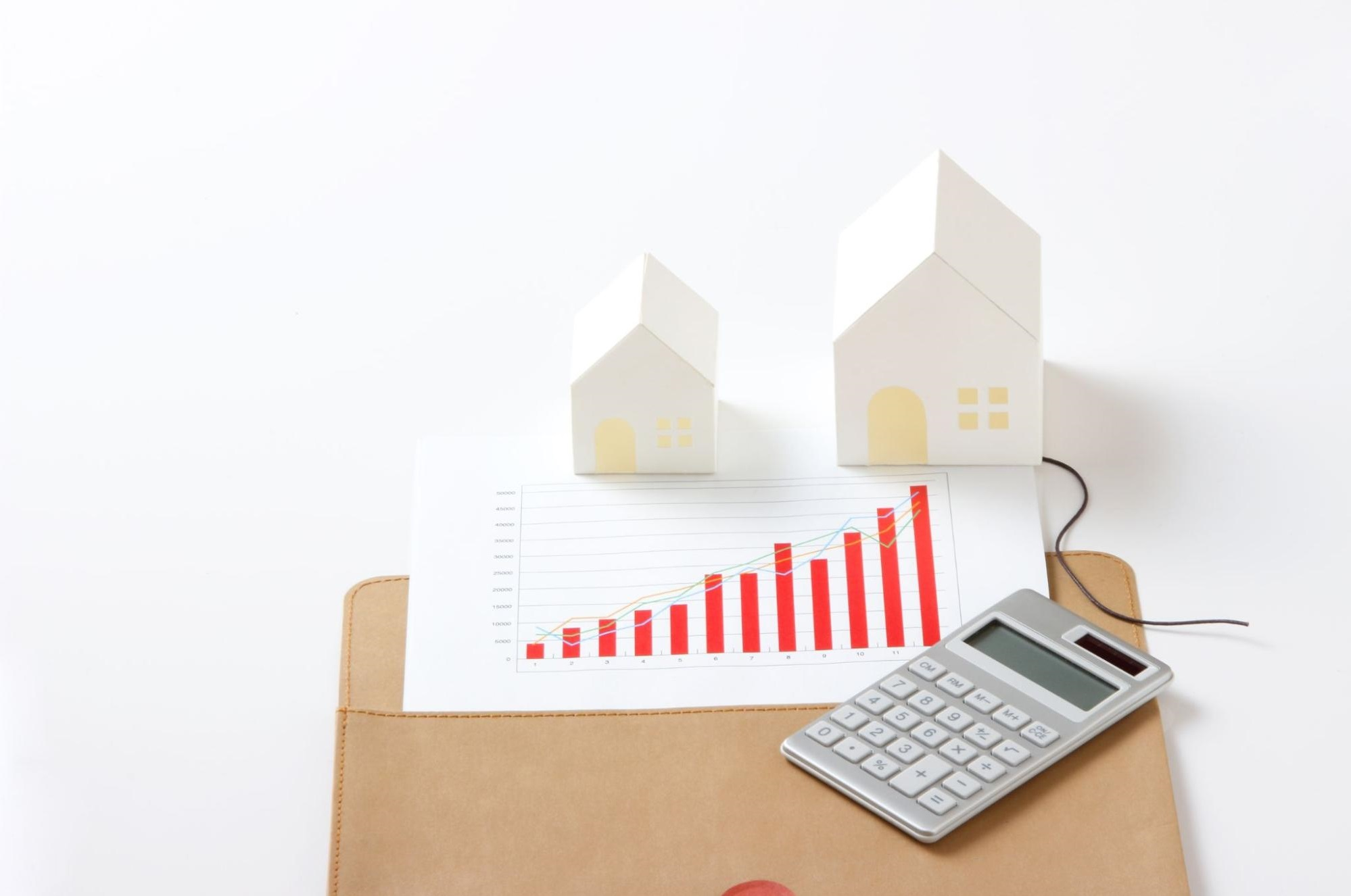 Paper houses and a calculator on top of a financial report