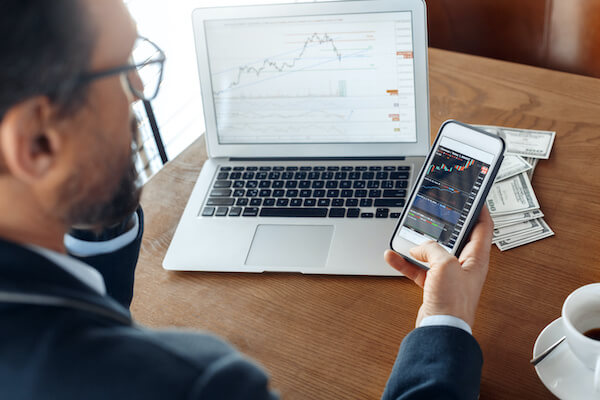 dividend rate: man looking at charts on his mobile phone and laptop