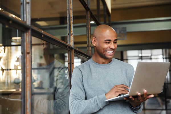 put vs call: man smiling while holding his laptop