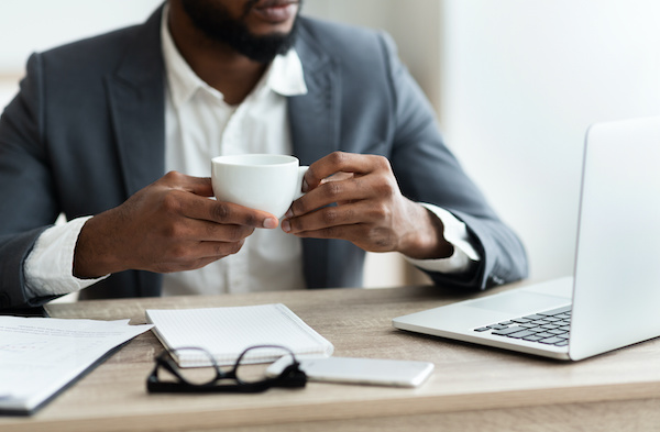 man working while having a cup of coffe