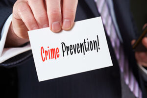 A businessman holding a business card with the words,  Crime Prevention, written on it.