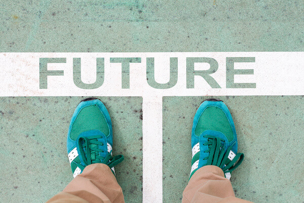 Person stepping into the word FUTURE