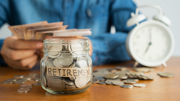 free retirement stock: person holding some cash and a jar full of coins on the table