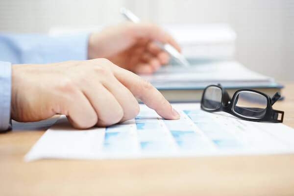 portfolio income: person pointing out some data on paper