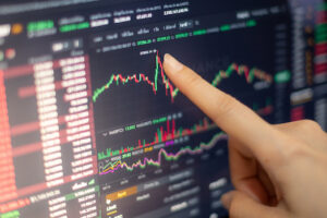 The business woman investor trading or stock brokers having a planning and analyzing with display screen and pointing on the data presented and deal on a stock exchange.