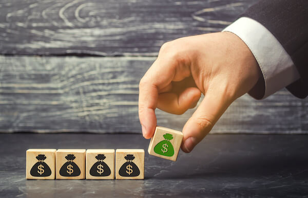 cash secured puts: person putting down a wooden cube