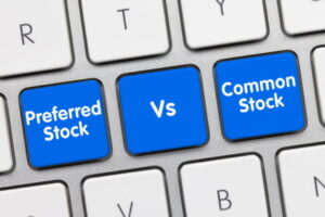 Preferred Stock Vs. Common Stock Written on Blue Key of Metallic Keyboard. Finger pressing key.