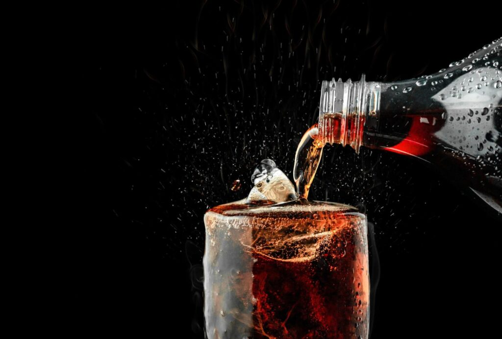 soda being poured over a glass with ice