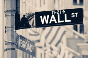 Vintage looking Wall street sign  in New York City with out of focus buildings and american flags on the background
