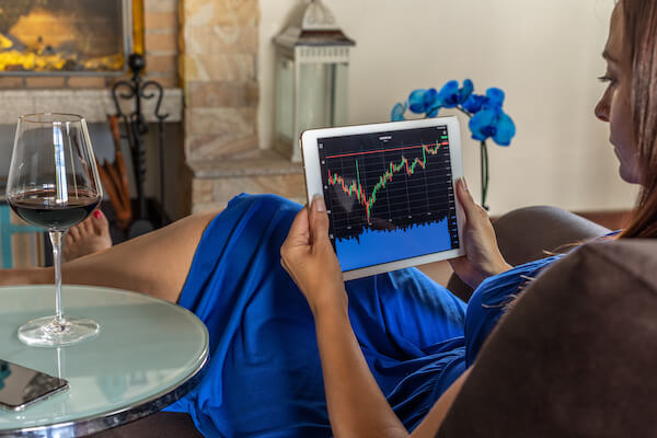What are dividends: woman looking at stock trends via her tablet