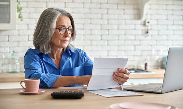 free retirement stock: woman reading documents on her desk